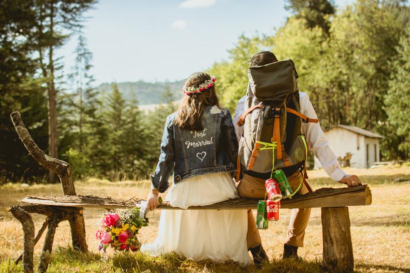 novios de espaldas novia con el bouquet y chaqueta de jean just married y novio con backpack y latas colgando