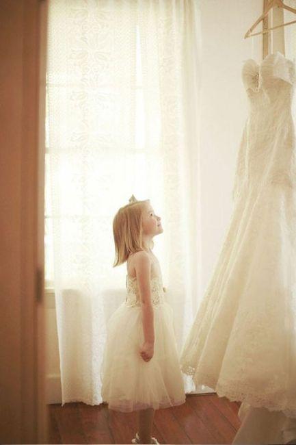 La niña de las aros mirando el vestido de la novia, imaginando cómo le quedará