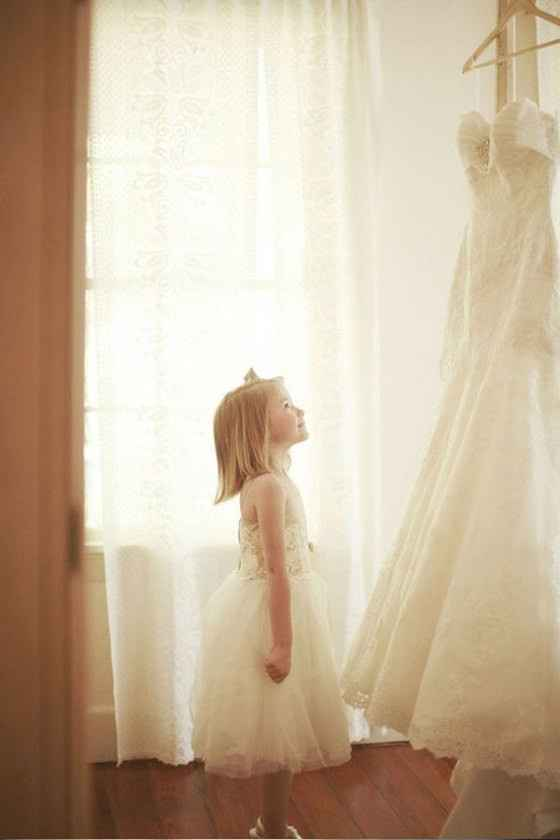 La niña de las aros mirando el vestido de la novia, imaginando cómo le quedará