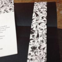 sobre negro con cinta de papel blanca y decoraciones en negro